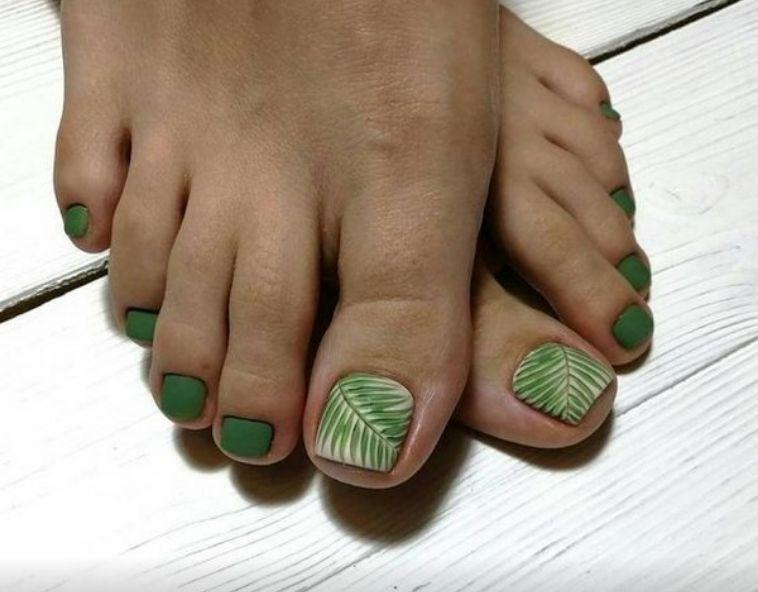 Матовый зеленый педикюр с узором-листочком на большом пальце