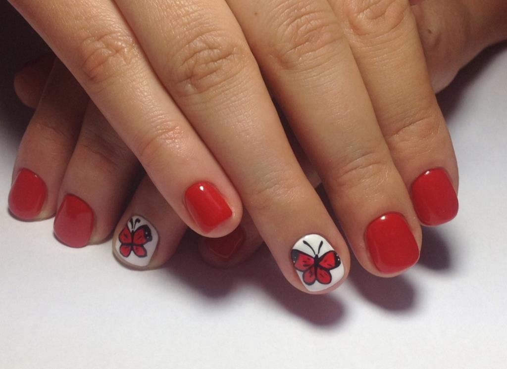 Алая бабочка на белом безымянном пальце и ярко красный маникюр